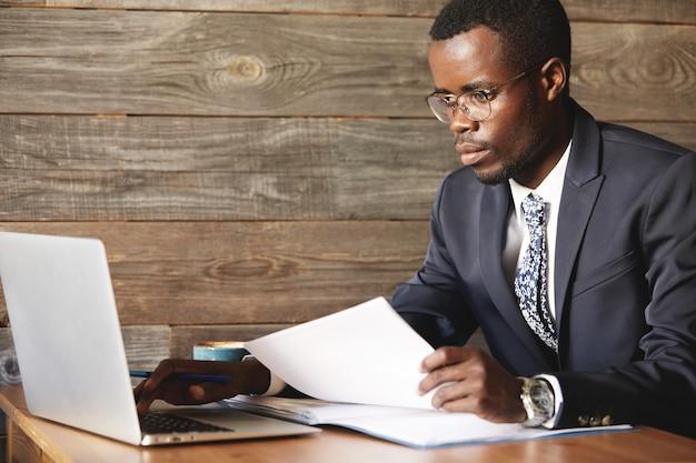 Wohlhabender top-manager im formellen anzug, der mit papieren unter verwendung eines laptops arbeitet