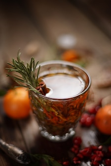 Wohlriechender fruchttee mit tangerinen, getrockneten zitronen und rosmarin auf einem holztisch. landhausstil.