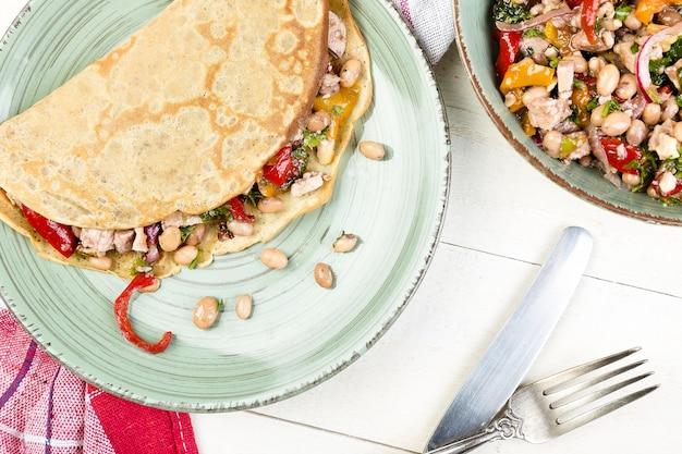 Wohlschmeckender buchweizen-pfannkuchen mit weißen bohnen. mexikanischer quesadilla. ansicht von oben.