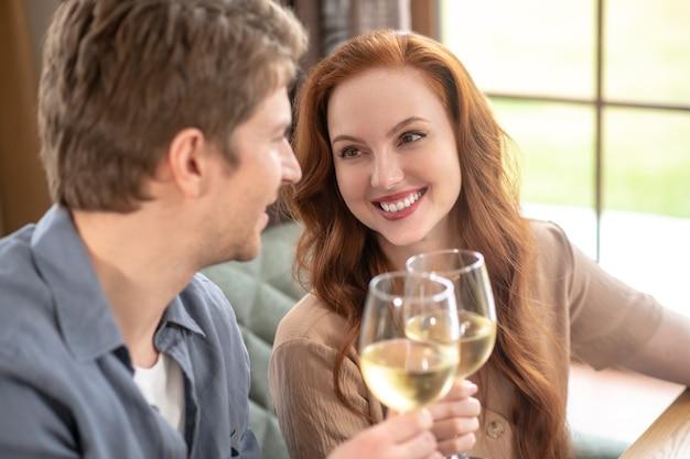 Wohlstand, toast. schöne junge fröhliche ingwerhaarige frau und aufmerksamer fürsorglicher mann mit weingläsern, die im restaurant sitzen und datum feiern celebrating