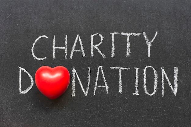 Wohltätigkeitsspendensatz handschriftlich auf schultafel mit herzsymbol statt o