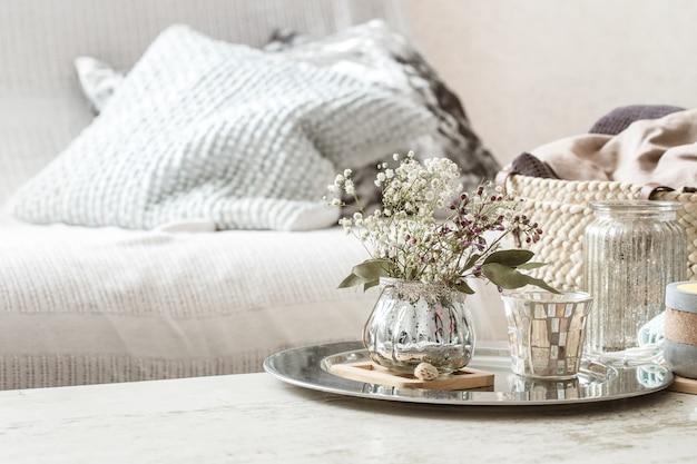 Wohnaccessoires im innenraum. eine türkisfarbene decke und ein weidenkorb mit einer vase mit blumen und kerzen