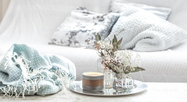 Wohnaccessoires im innenraum. türkisfarbene decke und weidenkorb mit einer vase mit blumen und kerzen