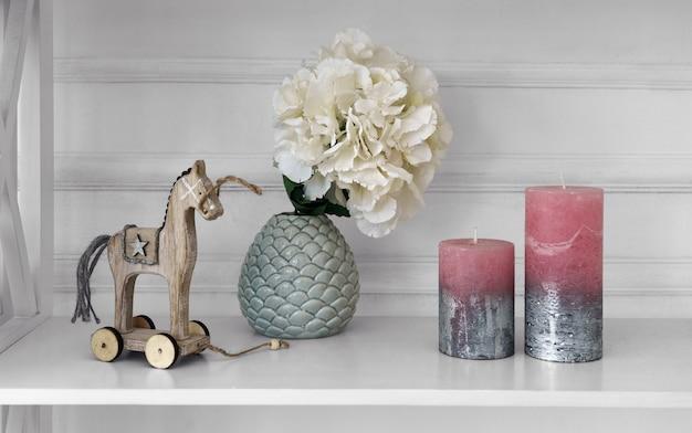 Wohnaccessoires vase und holzpferd neben kerzen