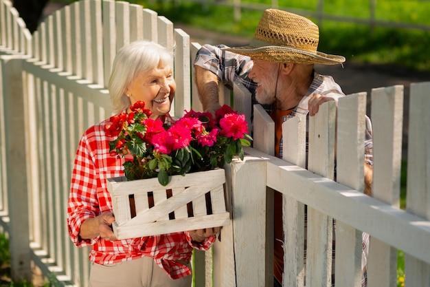 Wohnen in der nachbarschaft. fröhlicher pensionierter mann und frau, die in einer nachbarschaft leben und über blumen sprechen