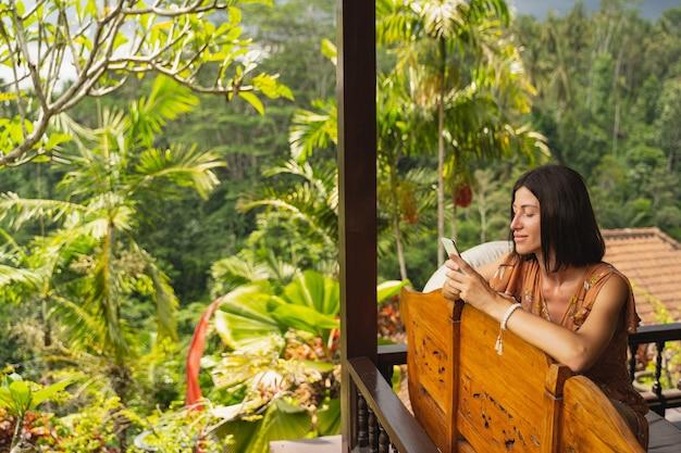 Wohnen in oase. nette junge frau, die positivität ausdrückt, während sie online kommuniziert, mit ihrem mobiltelefon mobile