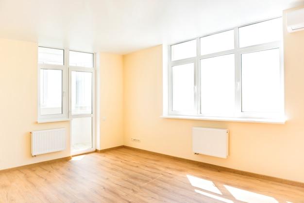 Wohninnenraum des leeren raumes mit holzboden und licht aus den großen weißen isolierten fenstern