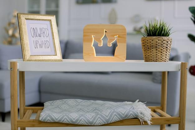 Wohnkultur, holzlampe. vorderansicht des kleinen tisches mit fotorahmen, dekorativer holzlampe mit schlossturmbild und grüner pflanze im weidenblumentopf.