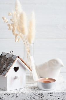 Wohnkultur im skandinavischen stil mit pampasgras-trockenblumen auf rustikaler wand im monochromen stil. duftkerzen und vogelhaus mit kopierraum