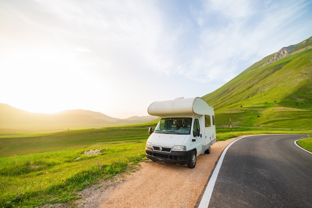 Wohnmobil am straßenrand in schöner landschaft. dramatischer himmel bei sonnenuntergang, malerische wolken über einzigartigem hochland und hügelkette in italien, alternatives vanlife-ferienkonzept.