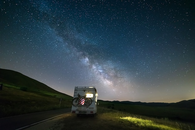 Wohnmobil am straßenrand in schöner nachtlandschaft unter den sternen. der milchstraßenbogen und die sterne über einem beleuchteten wohnmobil. campingfreiheit im italienischen apennin.