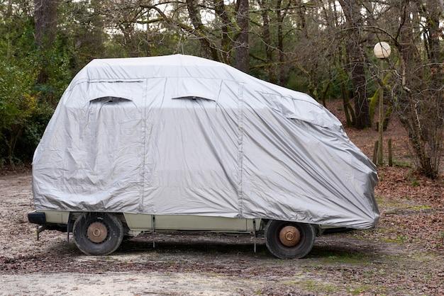 Wohnmobil mit grauer schutzhülle von stadthaus für nasses wetter in parkplatz stadt bedeckt