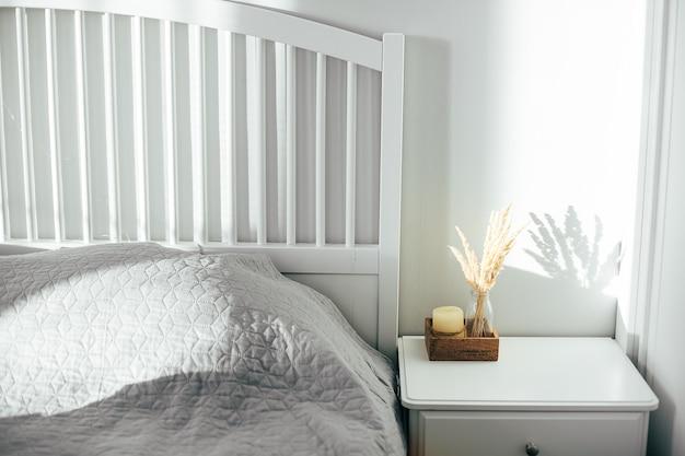 Wohnraum. skandinavisches schlafzimmer interieur. holztablett mit kerze und getrockneten blumen. natürlicher schatten.