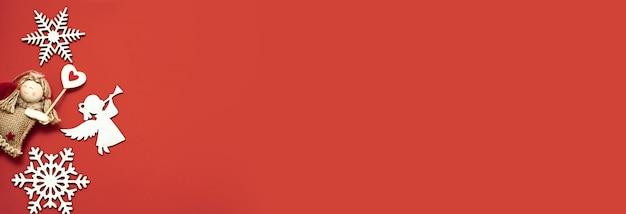 Wohnung lag auf rotem hintergrund. hölzerne schneeflocken und engel. handgemachte dekoration. 2020 neues jahr