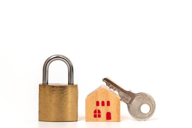 Wohnungsbaudarlehen und sicherheitskonzept. nahaufnahme des hölzernen hausspielzeugs mit hauptschlüsselschloss auf weißem hintergrund.