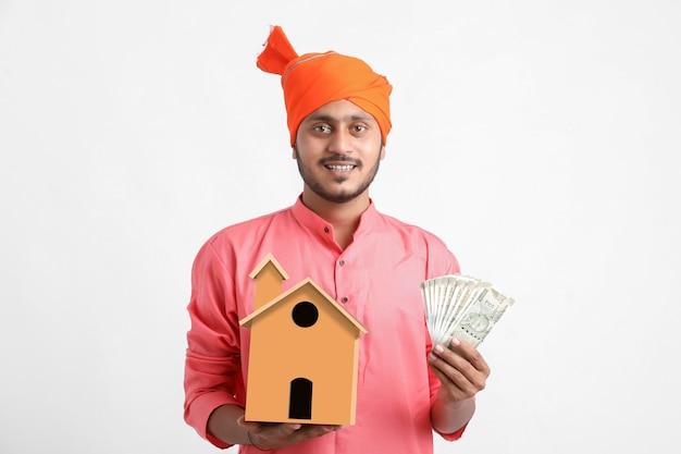 Wohnungsbaudarlehenskonzept indischer mann, der handgemachtes haus und währung in der hand hält