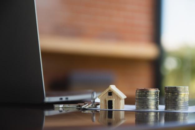 Wohnungsbaudarlehensmünzen stapeln sich auf tischcomputerseitenansicht hintergrundkonzept geldgeschäftsinvestitionen