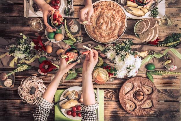 Wohnungsfest von freunden oder familie am festlichen tisch mit kaninchenfleisch, gemüse, kuchen, eiern, draufsicht.