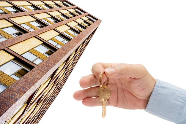 Wohnungsschlüssel in der hand eines mannes. haustürschlüssel aus messing. modernes gebäude, ansicht von unten. architektur in der modernen stadt. verkauf und vermietung von immobilien.