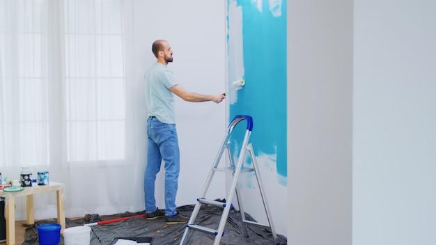 Wohnungswand mit weißer farbe mit rollbürste streichen. handwerker renovieren. wohnungsrenovierung und hausbau während der renovierung und verbesserung. reparieren und dekorieren.