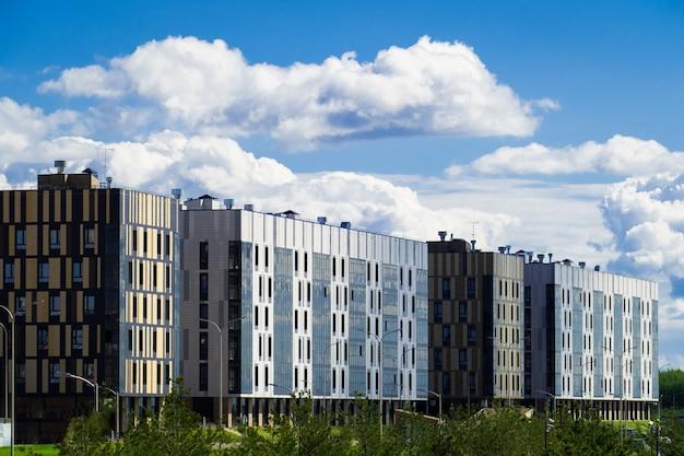 Wohnviertel mit modernem sechsstöckigem gebäude auf dem hintergrund von sich hin- und herbewegenden wolken