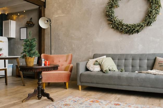 Wohnzimmer im haus dekoriert für weihnachten und neujahr grauer sofastuhl weihnachtskranz