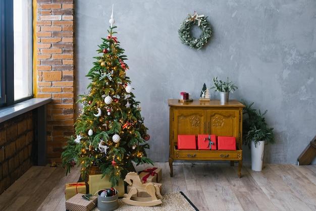 Wohnzimmer interieur im weihnachtsloftstil. weihnachtsbaum mit geschenken und kommode