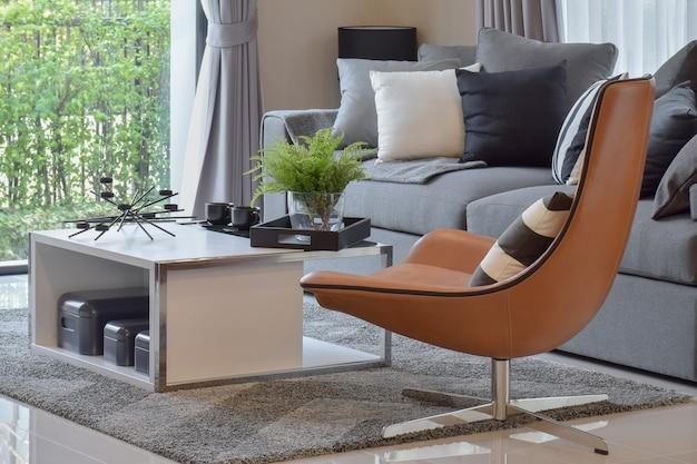 Wohnzimmer mit anlage im vase und in den schwarzen musterkissen auf modernem lederstuhl