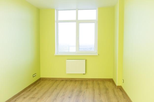 Wohnzimmerinnenraum des grünen leeren raumes mit holzboden und licht vom großen fenster