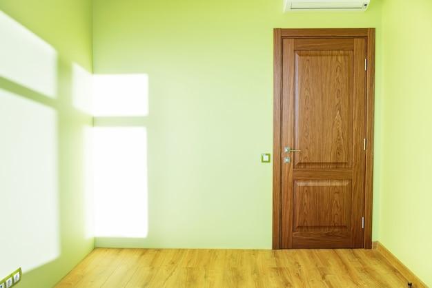 Wohnzimmerinnenraum des grünen leeren raumes mit tür und holzboden