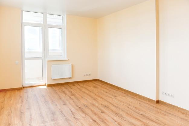 Wohnzimmerinnenraum des leeren raumes mit holzboden und licht vom großen fenster