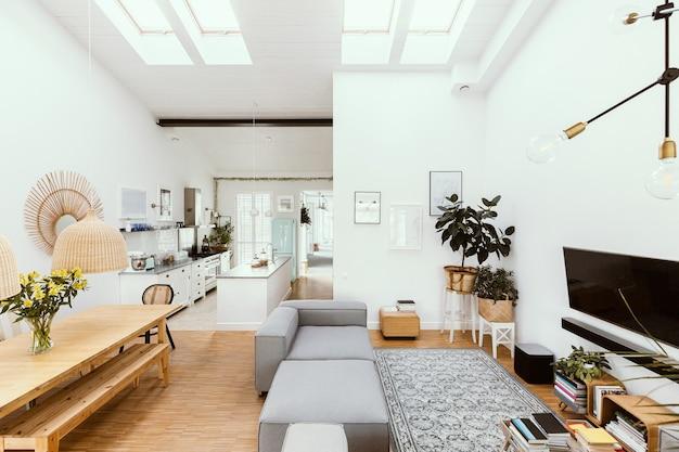 Wohnzimmerinnenraum des offenen raumes mit esszimmertisch der küche und grauer couch