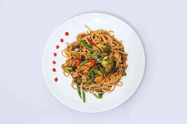 Wok-essen auf einer weißen keramikplatte ist lecker und frisch mit sauce auf einem hellen, isolierten hintergrund