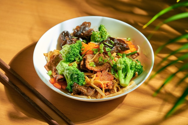 Wok-nudeln mit gemüse und rindfleisch in einer schüssel. chinesische küche