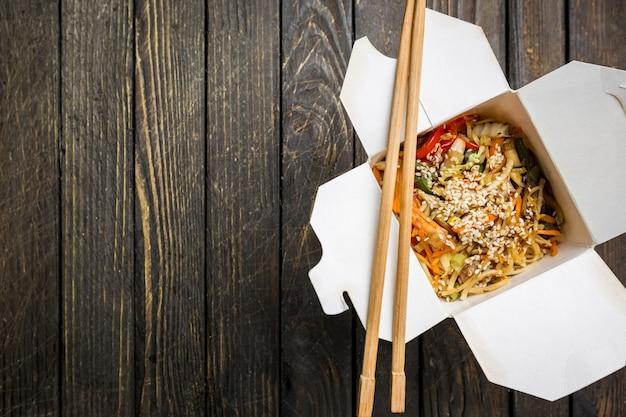 Wok-nudeln udon und reis mit meeresfrüchten und hühnchen in einer schachtel auf schwarz