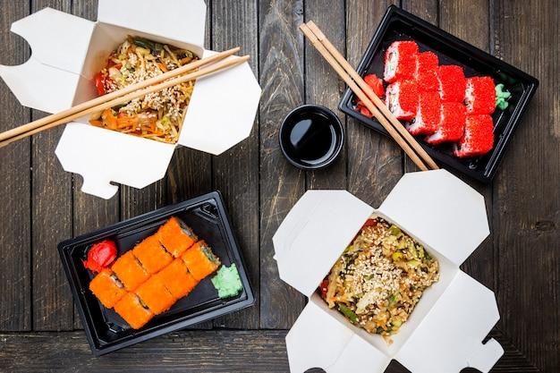 Wok-nudeln udon und reis mit meeresfrüchten und hühnchen in einer schachtel und sushi auf schwarz. mit stäbchen und sauce