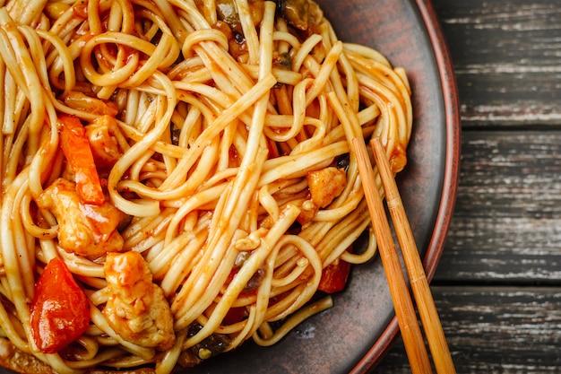 Wok udon braten sie nudeln mit hühnerfleisch in süß-saurer soße auf dunkelheit an