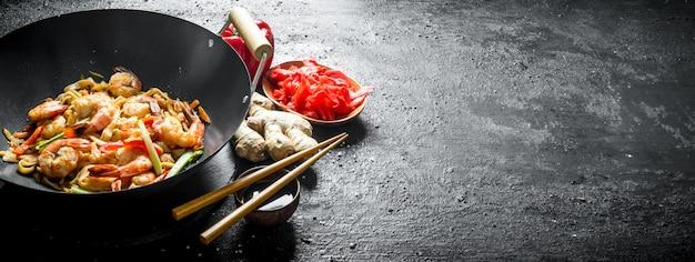 Wok udon nudeln mit ingwer, sojasauce und paprika. auf schwarz rustikal