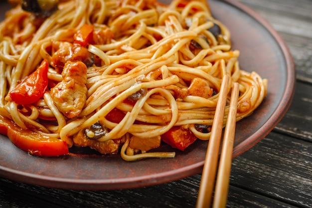 Wok udon rühren braten nudeln mit hühnchen und gemüse in teller und essstäbchen