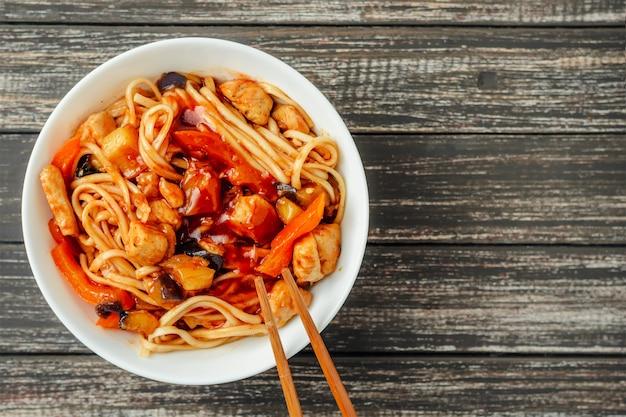 Wok-udonnudel mit huhn und gemüse in einer weißen platte auf hölzernem hintergrund