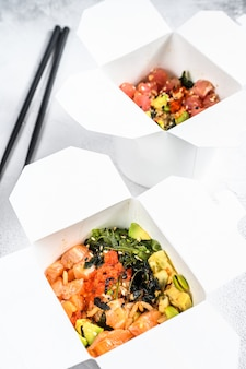 Woknudel in papierbox mit gemüse, lachs und thunfisch. straßenessen zum mitnehmen. weißer hintergrund. draufsicht