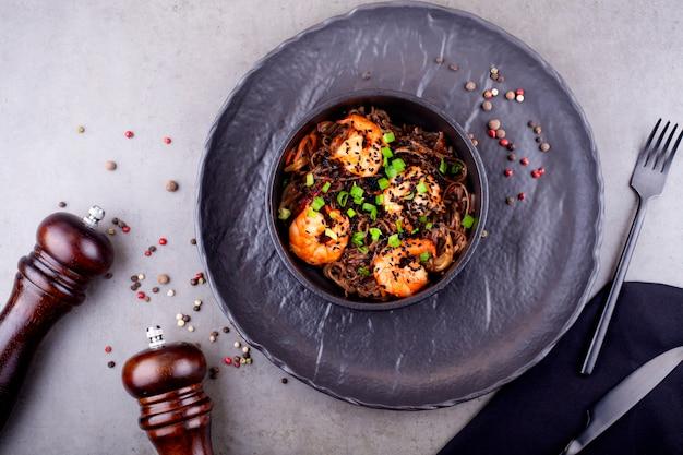 Woknudeln mit garnelen, in einem schwarzen teller mit erbsen verziert, auf grauem hintergrund. das konzept der asiatischen küche.