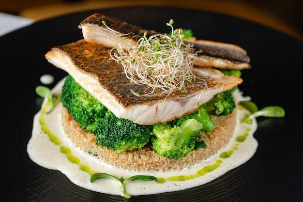 Wolfsbarschfilet mit brokkoli und quinoa auf schwarzem teller