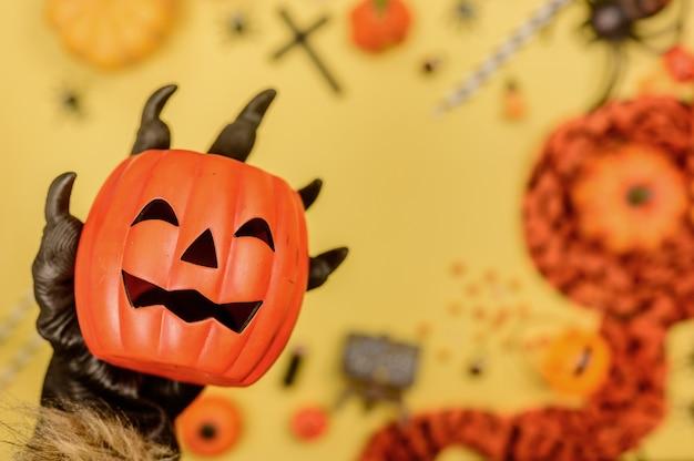 Wolfshand, die kürbisgesicht mit halloween-hintergrund hält. süßes oder saures in der herbst- und herbstsaison.