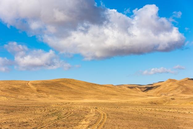 Wolken am blauen himmel über bergen mit getrocknetem gelbem gras