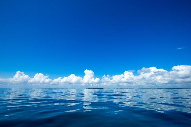 Wolken am blauen himmel über ruhigem meer mit sonnenlichtreflexion