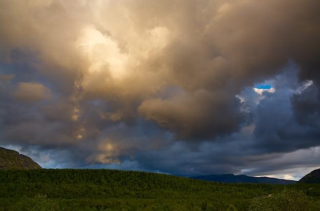 Wolken am himmel über den bergen, die bei sonnenuntergang von der sonne beleuchtet werden.