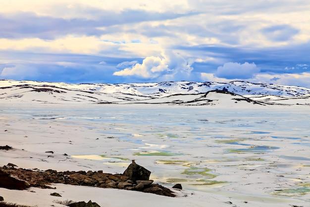 Wolken über den gefrorenen schneebedeckten bergen und dem see