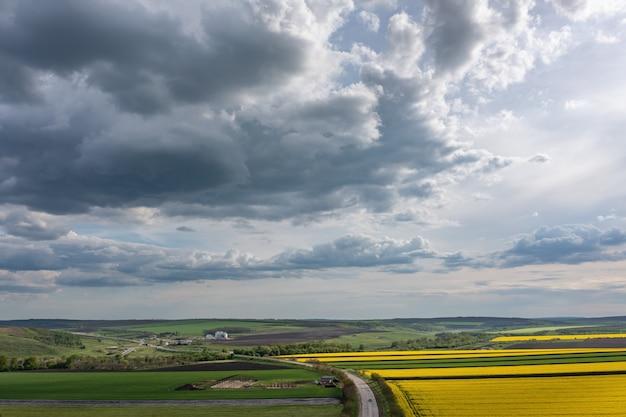 Wolken über landwirtschaftlichem rapsfeld luftaufnahme
