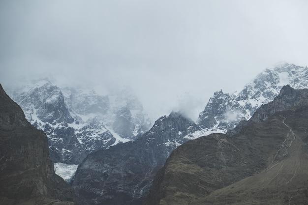 Wolken und nebel bedeckten schnee mit einer kappe bedeckten karakoram-gebirgszug, pakistan.